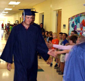 Senior Griffin Martin gets a high five from a lower school student